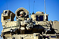 A U.S. Army soldier keeps watch from the hatch of his Bradley Fighting Vehicle at the National Training Center in Fort Irwin 130224-D-DB155-008.jpg