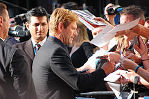 A caucasian male is signing autographs for fans. He has blond hair, and is wearing a black suit jacket. Visible in the background are other people.