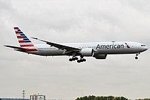 Ein langes graues Flugzeug steht kurz vor der Landung mit ausgefahrenem Fahrwerk
