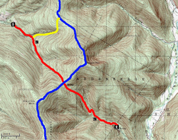 A green topographic map with brown contour lines showing Balsam Mountain with Big Indian Hollow on the east. Winding red and blue lines intersect below the summit, and a short yellow line connects them in the upper left quadrant