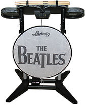 "A drum set video game controller with four elevated drum pads mounted on a frame, along with a bass pedal attached to a bottom crossbar. A thin panel, stating ""Ludwig"" and ""The Beatles"" is mounted to the front. The drum pads are colored in a metallic gray pattern, while most of the rest is either black or gray."