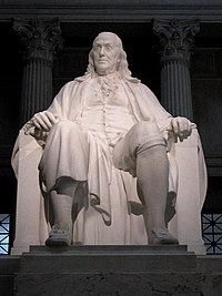 Seated statue of Benjamin Franklin in white marble