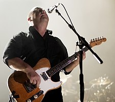 Black Francis playing guitar onstage in front of a microphone, looking up