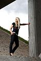 Blond woman in black clothing under cement pilars 01.jpg