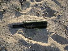 Una bottiglia sulla sabbia.