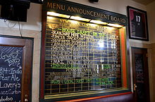 Blackboard with labels for names of train and destinations, but lists names of beers and other beverages instead