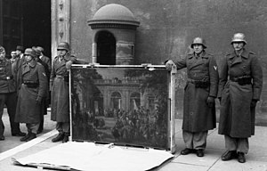 Nazi plunder - German soldiers of the Hermann Göring Division posing in front of Palazzo Venezia in Rome in 1944 with a picture taken from the Biblioteca del Museo Nazionale di Napoli before the Allied forces' arrival in the city Carlo III di Borbone che visita il papa Benedetto XIV nella coffee-house del Quirinale a Roma by Giovanni Paolo Pannini (Museo di Capodimonte inv. Q 205)