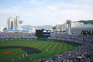 An open roof crowded baseball stadium with a match in progress.