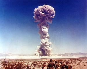 A mushroom cloud rise over the desert, watched by seven men in uniforms.