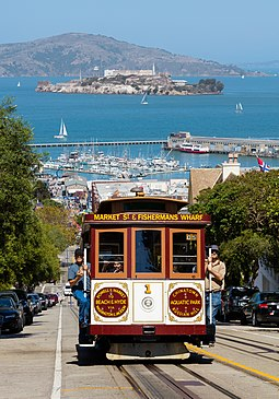 A cable car ascending Hyde St, with Alcatraz on the bay behind Cable Car No. 1 and Alcatraz Island.jpg