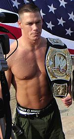 A man with a championship belt on his shoulder, with the American flag in the background.