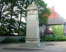 A four-sided stone column topped with a lion lying down, in a small semi-circular paved garden area.