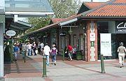 A busy pedestrian walkway through an open air shopping mall