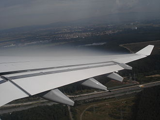 Wing - Condensation in the low pressure region over the wing of an Airbus A340, passing through humid air