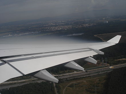 Condensation forming in the low pressure zone above the wing of an aircraft due to adiabatic expansion Cloud over A340 wing.JPG