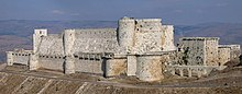 photograph of 12th-century Hospitaller castle of Krak des Chevaliers in Syria showing concentric rings of defence, curtain walls and location sitting on a promontory.