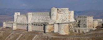 Photographie d'un imposant château fort composé de deux rangées de murailles situé dans un paysage valonné recouvert de maquis