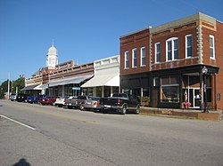 Broad Street storefronts in downtown Crawfordville, Georgia, with Taliaferro County Courthouse in the distance