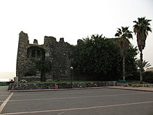 Ruins of a castle, with palm trees and foliage