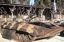 Dois veículos blindados danificados.  Uma bandeira israelita está ao lado deles.