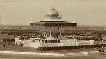 Vaste estrade blanche surmontée d'un chapiteau de style indien et entourée de milliers de soldats et de spectateurs