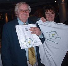 A man and a woman holding white T-shirts in front of themselves