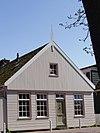 foto van Houten huis met puntvormig voorschot ten dele in baksteen vernieuwde zijwanden