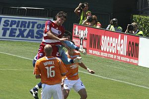 A Dallas FC player jumping in the air versus two Houston defenders and their goalkeeper