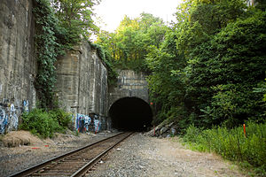"Long Dock Tunnel - Eastern portal above which are three engraved stones. The first lists the officers and engineers of the company. The seconds reads ""Long Dock Company founded 1856"". The third reads ""Bergen Tunnel completed 1861""."