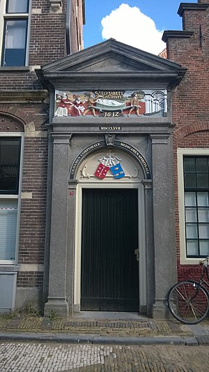 St. Elisabeth Gasthuis, Haarlem - Newly painted Elisabeth Gasthuis Poort doorway next to the old pensioner's homes, showing old gable stone from 1612 with a patient in a basket on a stretcher (Dutch: lappenmand)