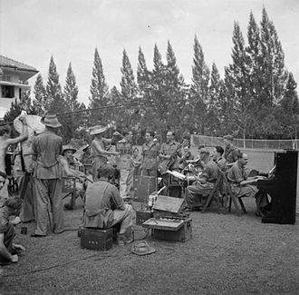 Calling Blighty - A Calling Blighty film unit sets up a shot with the dance band of the Cameronians in Singapore 21 February 1946. On the right of the camera is the producer, Captain L Hamilton-Webb, while around the microphone are Staff Captain Jackson and brothers Louis and Ted De Rosa.