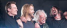 John Paul Jones, Taylor Hawkins, Jimmy Page, and Dave Grohl hugging and smiling onstage