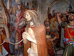 Statue montrant un homme fouetté et saignant, emmené lié par des soldats.
