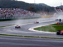 Four Formula One cars are turning left into a corner with spray being lifted from the ground by their tyres.