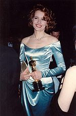 Portrait of a woman in her early thirties wearing a light blue satin evening gown. She is clutching a golden statuette.
