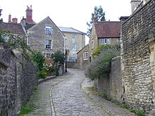Narrow street between stone walls and houses