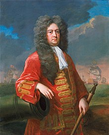 Painting of a middle-aged man wearing a long flowing wig and a red coat with gold frogging, resting his right arm on a cannon and holding a rammer in his left hand. A fleet of ships is visible in the background.