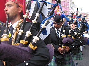 Drone (music) - Highland bagpipes, with drone pipes over the pipers' left shoulders