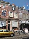 foto van Huis met schilddak en eenvoudige lijstgevel met rode strekken boven de vensters, welke schuiframen bevatten. Etalage