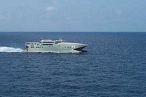 A warship-grey catamaran travelling at speed (from right to left) on the open sea