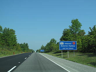Ontario Highway 416 - Highway 416 is commemorated as the Veterans Memorial Highway. Signs placed along the length of the highway in English and French (in background) indicate this along with the phrase Lest we forget.