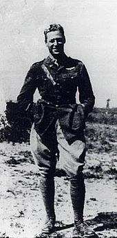 A man standing in a relaxed pose dressed in military attire.