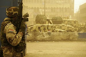 Siege of Sadr City - An Iraqi army soldier from the 42nd Brigade, 11th Iraqi Army Division takes cover and points to where his men need to go during a firefight with armed militiamen in the Sadr City district of Baghdad April 17, 2008