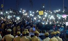 Students use their mobile phone flashlights to illuminate their protest after street lights are turned off by power company TNEB.