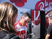 Photographie présentant Jérôme Pineau devant le bus de l'équipe pendant le Tour de France 2004.