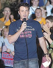 Ben Affleck speaking into a microphone while wearing a Kerry/Edwards campaign tshirt