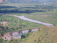 Photograph of confluence of the Kagera and the Ruvubu, with the Rwanda-Tanzania border post in foreground, taken from a nearby hilltop