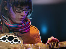 A bespectacled woman plays a guitar.