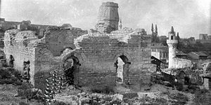 Kasım Agha Mosque - A view from south of the mosque in ruin after the fire of 1919. To its right in the background the minaret of the Odalar Mosque, also burned. The distant minaret belongs to the Kariye Mosque.