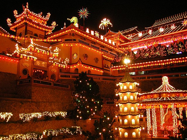 Temple at night illuminated with light from decorations.